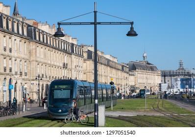 Bordeaux, France - 26th September, 2018: cyclist waiting for Electric Tram passing through quai Richelieu in downtown Bordeaux.