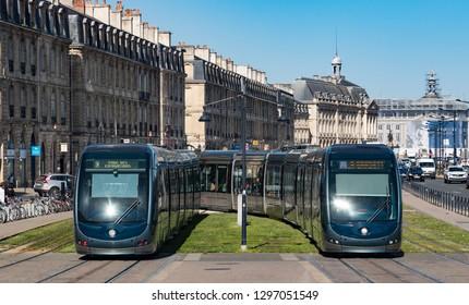 Bordeaux, France - 26th September, 2018: Electric Trams passing through historic buildings on quai Richelieu in downtown Bordeaux.