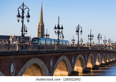 Bordeaux, France - 27th September, 2018: Tram and people crossing Pont de Pierre bridge in the city of Bordeaux during morning.