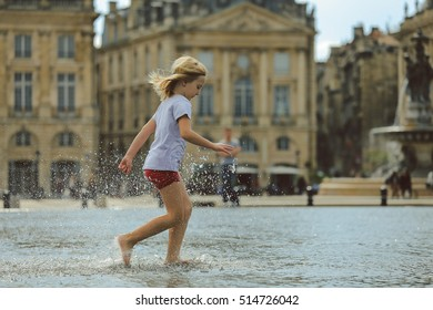 BORDEAUX, FRANCE - 3 October, 2016 : Fun kid playing splash water at  Bordeaux water mirror in summer, France