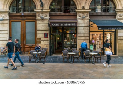 Bordeaux, France, 8 may 2018 -tourists and locals passing a Cafe Brasserie at the main shopping street 'Rue Sainte-Catherine'