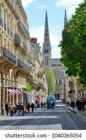 BORDEAUX, FRANCE - APRIL 25 2016: The passers and the tram are in the street of the ancient French city with the cathedral in the background. BORDEAUX, FRANCE - APRIL 25 2016.