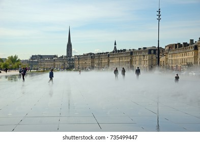 BORDEAUX, FRANCE - APRIL 25 2016: The people are in the fog of the reflecting pool Miroir d'eau in the most recognizable square Place de la Bourse in the French city BORDEAUX, FRANCE - APRIL 25 2016.