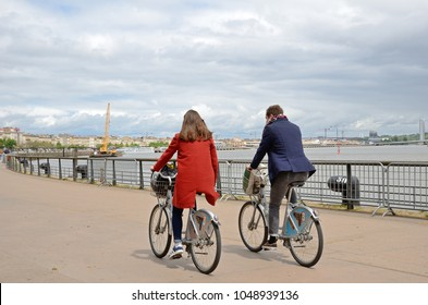 BORDEAUX, FRANCE - APRIL 26 2016: A woman a man rides a public bike along the river in the quay of the French city Bordeaux. BORDEAUX, FRANCE - APRIL 26 2016.