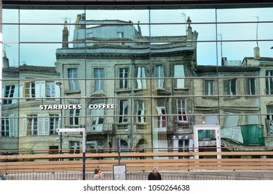 BORDEAUX, FRANCE - APRIL 26 2016: Glass surface of the modern building of Starbucks reflect the traditional townhouses in the historical part of the French city. BORDEAUX, FRANCE - APRIL 26 2016.