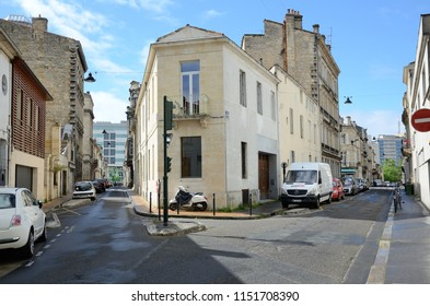 BORDEAUX, FRANCE - APRIL 26 2016: Modern vehicles are parked in the ancient empty street in the French city Bordeaux. BORDEAUX, FRANCE - APRIL 26 2016.