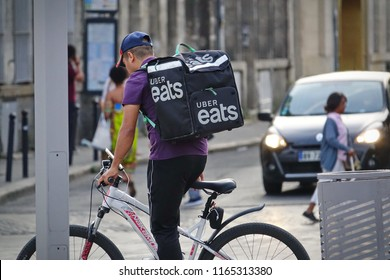 Bordeaux, France - August, 2018: Food supplier with Uber Eats backpack riding a bike on the street