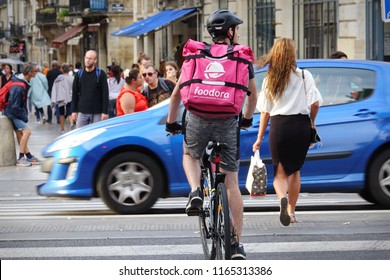 Bordeaux, France - August, 2018: Food supplier with Foodora backpack riding a bike on the street