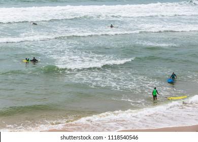 BORDEAUX, FRANCE - JUNE 13, 2017: Unrecognisable surfers in the water on the Atlantic coast of France near Lacanau-Ocean, Bordeaux, France