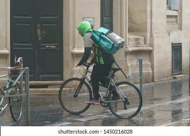 Bordeaux / France - June 21, 2019: Lifestyle of big city in rainy summer day. One caucasian student works as a delivery man for ready to eat food. He ship orders on bike in rain. European street life