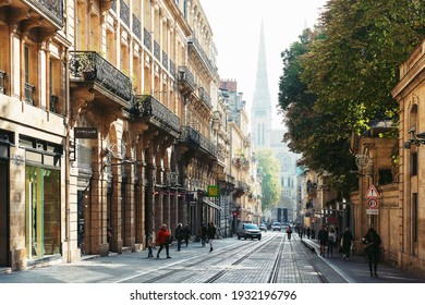 Bordeaux, France. October 29, 2019. Morning street of the ancient city with tram tracks, hurrying pedestrians and a view of the beautiful cathedral in the fog.