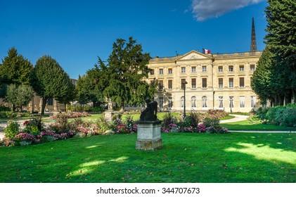 """BORDEAUX, FRANCE,  public park """" Jardin de la Mairie """" center town Bordeaux with ancient historic monument, statues, wide lawn, flowers, french flag"""