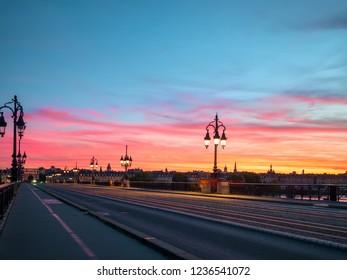 Bordeaux Stone Bridge (Pont de Pierre) and amazing sunset sky over the Bordeaux city, France.