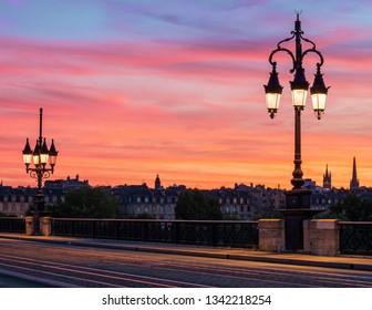 Bordeaux Stone Bridge (Pont de Pierre) with beautiful streetlights and amazing sunset sky over the Bordeaux city, France.