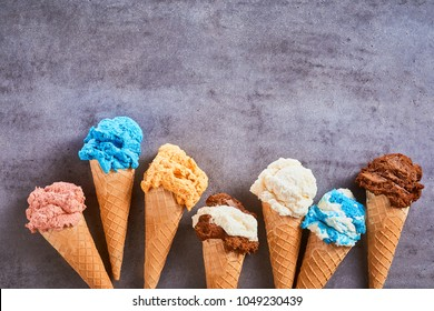 Border of assorted flavours of gourmet artisanal ice cream served in sugar cones over textures grey slate with copy space