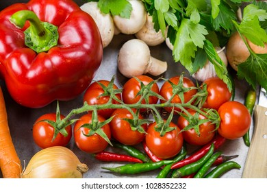 Border of assorted fresh healthy farm vegetables on a rustic blue wood background with central copy space in an overhead view