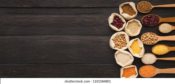 Border of assorted gluten free grains in cloth bags and spoons on rustic wooden background, copy space, top view