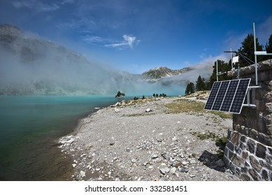 The border of Aubert lake in Neouvielle Natural reserve, the service cabin at right equipped with the solar cell panel, the lake and mountain slopes hided with the mist, Midi-Pyrenees, France