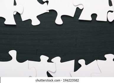 A border of blank white jigsaw puzzle pieces on a blackboard with copy space