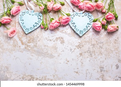 Border with blue hearts and pink roses flowers on grey vintage textured background. Floral still life.  Selective focus.