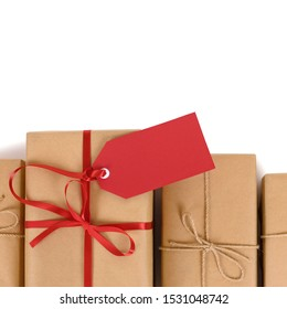 Border of brown paper parcels, one unique with red ribbon bow and gift tag or label, isolated on white background