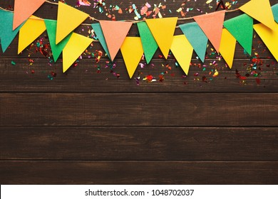 Border of colorful paper flags garland and confetti on rustic wood. Birthday party decoration background, top view, copy space. Mockup for greeting card