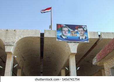 Border crossing Syria – Jordan. August 1st 2010.  Border entrance gate with Syrian flag and picture of Syrian royals Hafiz al-Assad and president Bashar Hafiz al-Assad