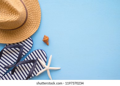 Border design flat lay with copy space. Tropical beach summer holiday vacation template banner with beach summer accessories (straw hat, flip flop) for traveling on blue wooden panel background.