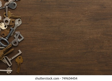 Border of different new and vintage keys and bunches on wooden background. Safety and security concept, top view with copy space