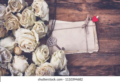 border of dry white roses, stack of old postcards tied with rope, key on chain, on old wooden table, vintage retro style image