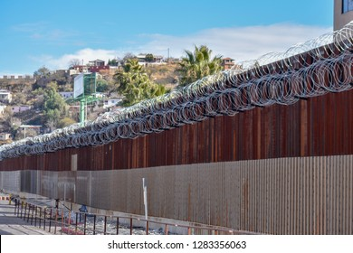 Border fence along the United States and Mexico border in Nogales, Arizona. Mexico is just beyond the fence. The constantine wire was recently added to the fence.
