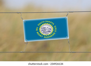 Border fence - Old plastic sign with a flag - South Dakota