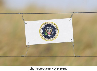 Border fence - Old plastic sign with a flag - Presidential Seal