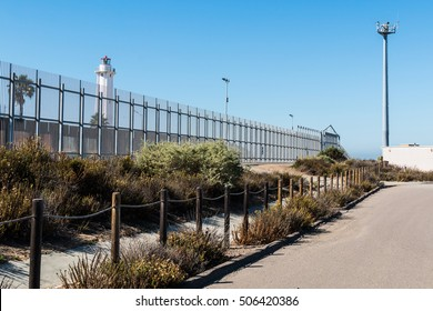 Border fence separating San Diego, California and Tijuana, Mexico, with El Faro de Tijuana lighthouse on the Mexico side and a security tower with cameras and motion sensors on the US side.