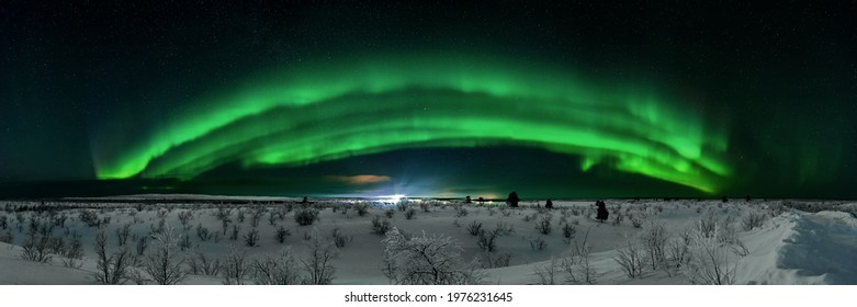 border Finland Norway - 02 24 2020: epic panorama of northernlights dancing over the border of norway and finland at the nightsky