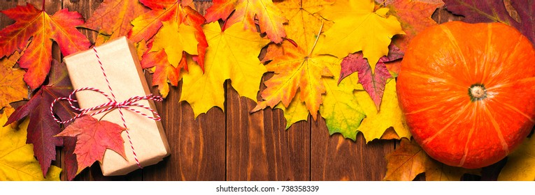border frame of colorful autumn leaves on wooden background with gift and pumpkin banner