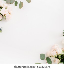 Border frame made of beige rose flowers, eringium flower, eucalyptus branches on white background. Flat lay, top view. Floral background