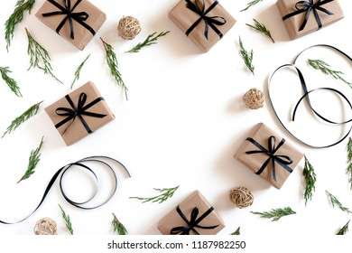 Border frame made of conifer tree branches, atlas ribbons, gift boxes packed in kraft paper on a white background