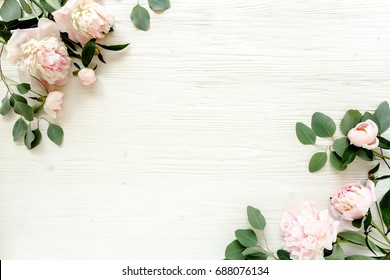Border frame made of pink and beige peonies flower buds, eucalyptus branches and leaves isolated on white wooden background. Flat lay, top view. Frame of flowers.