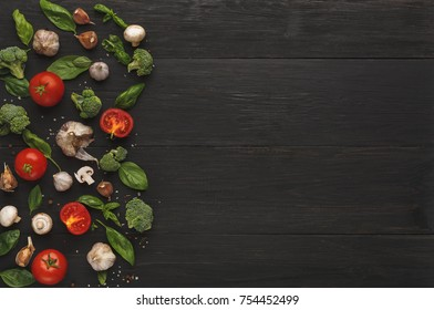 Border of fresh organic vegetables on wood background. Cherry tomatoes, garlic, sea salt and green basil leaves on rustic kitchen table, top view with copy space. Cooking ingredients