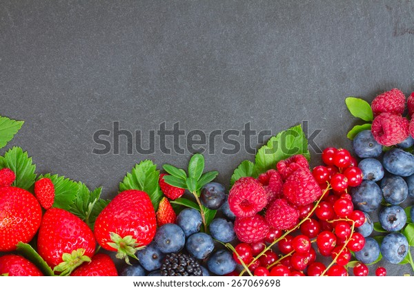 border  of fresh ripe  berries with green  leaves with copy space  on black stone background