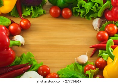 Border from fresh vegetables on a wooden background.