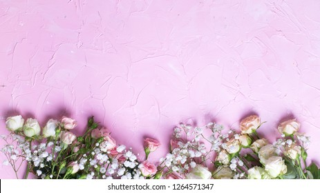 Border from fresh white gypsofila and white rose flowers on  pink textured background. Top view. Place for text.