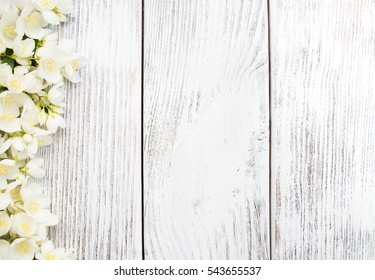 Border with jasmine flowers on a wooden background
