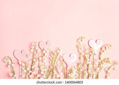 Border of lily of the valley flowers with love hears on a pink background. Copy space, top view.