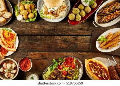 Border of Mediterranean dishes and bread on table. Copy space in middle over dark wooden surface.