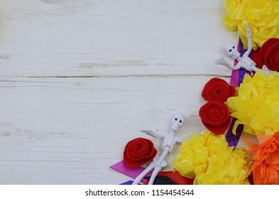 Border for Mexican holiday celebration Day of the Dead. Includes a sugar skull party mask and skeleton favors, paper and felt flowers and colorful ribbons on a rustic white-washed wooden background