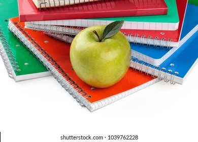 Border of notebooks  and green apple. Isolated on white background.