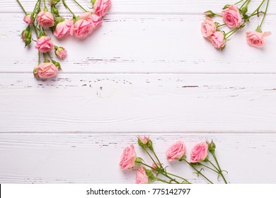 Border from  pink roses flowers  on  white wooden background. Floral still life.  Selective focus. View from above.