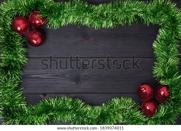 Border of red christmas baubles and green tinsel on a dark wooden background, with room for copy space